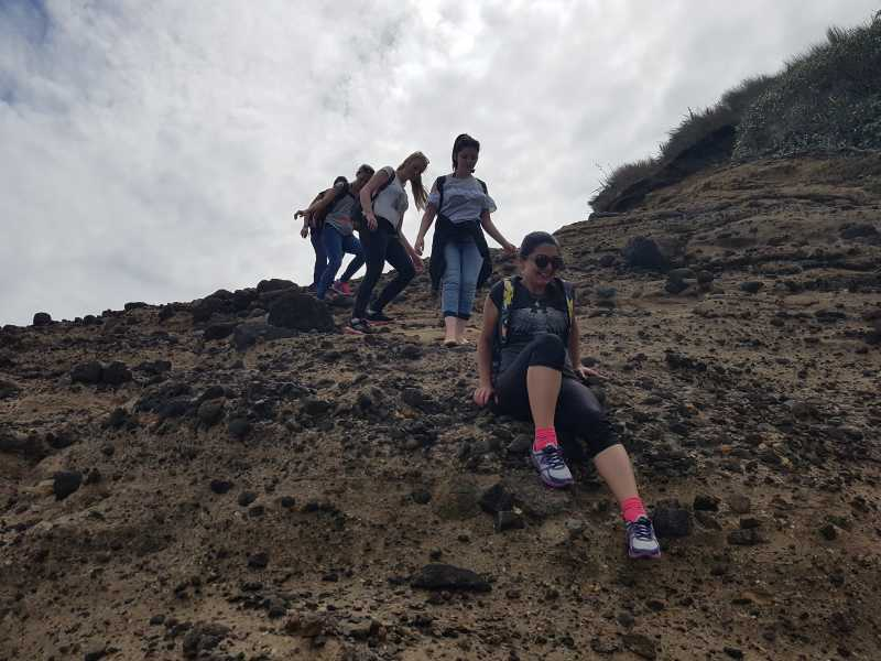 Climbing rocks at Piha Beach