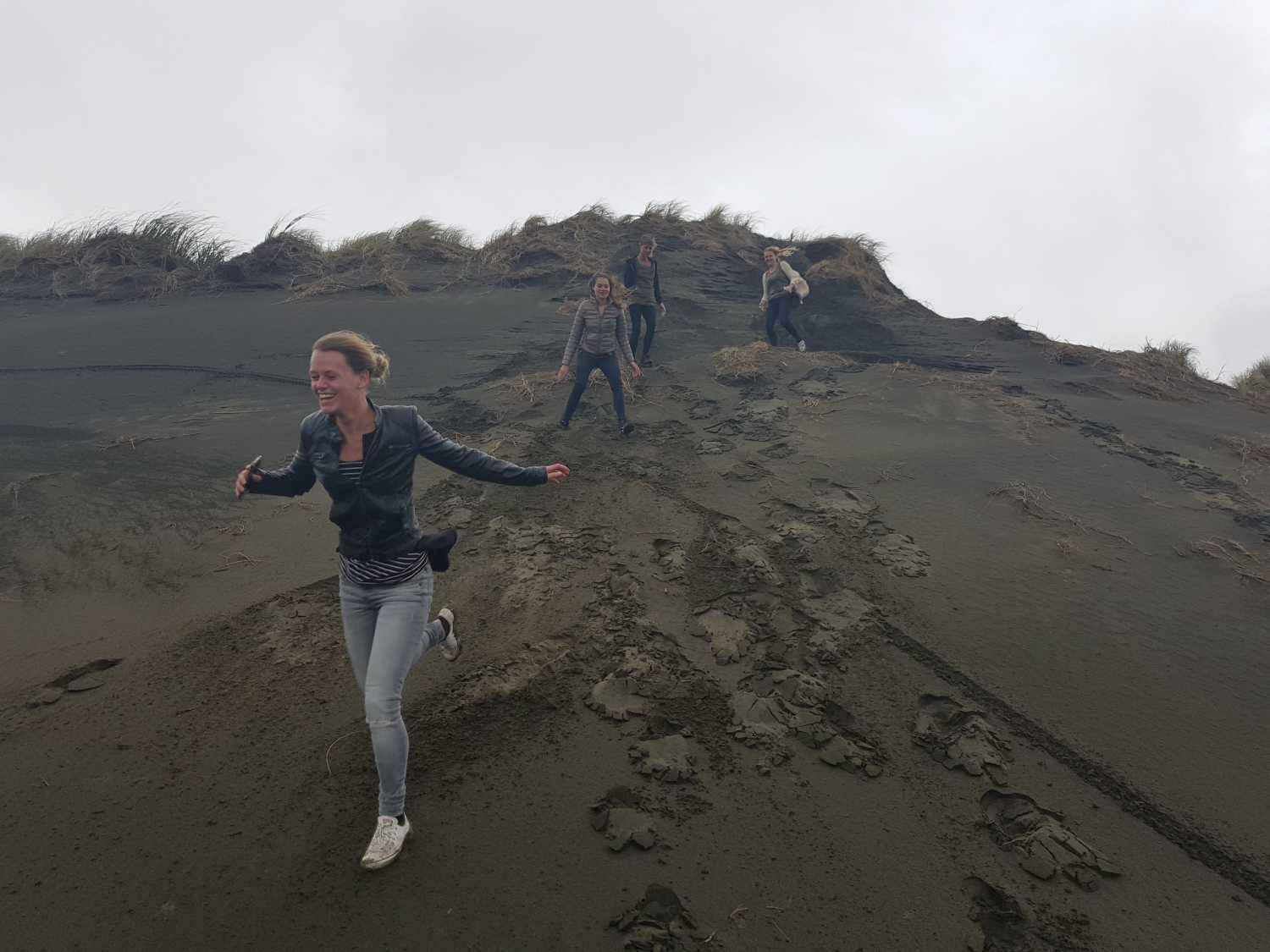 Tour group runs the dunes at Muriwai