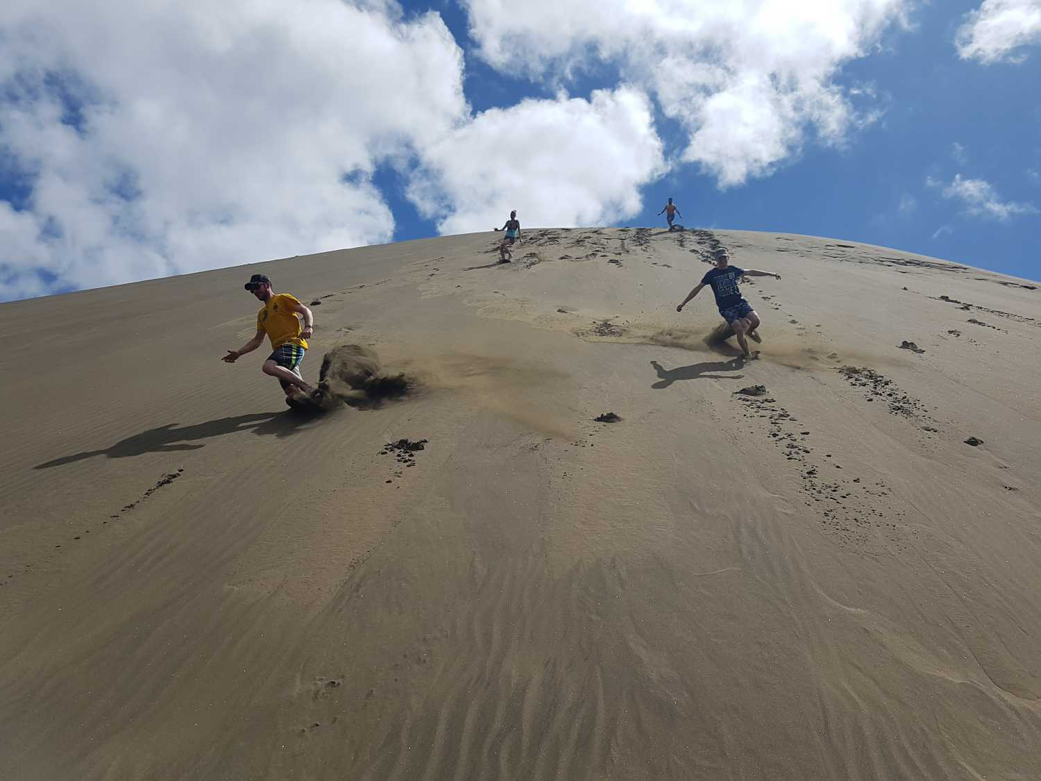 Adventure group sprints the large dune at Bethells