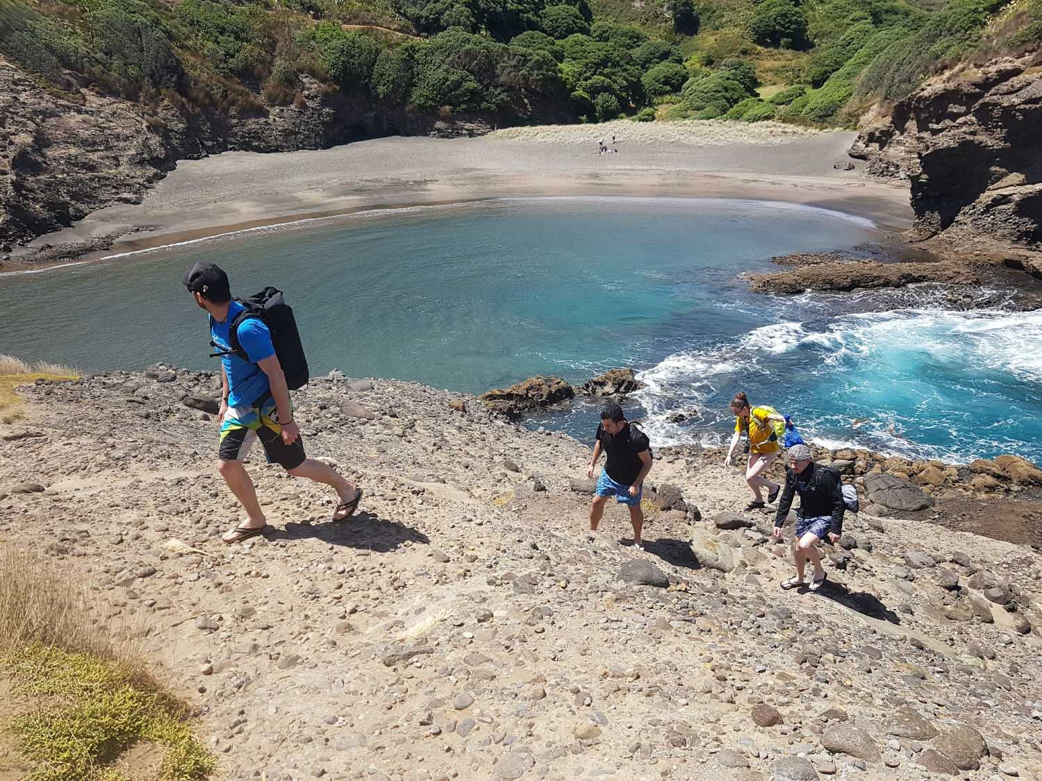 Tour group hikes over Piha Cliffs