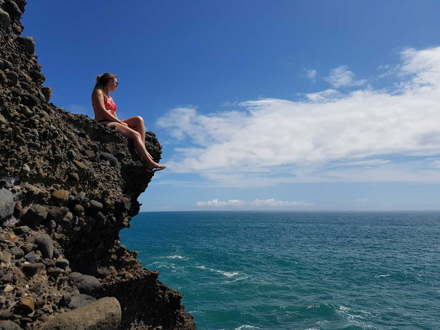 Girl chilling on the cliff tops at Piha Beach