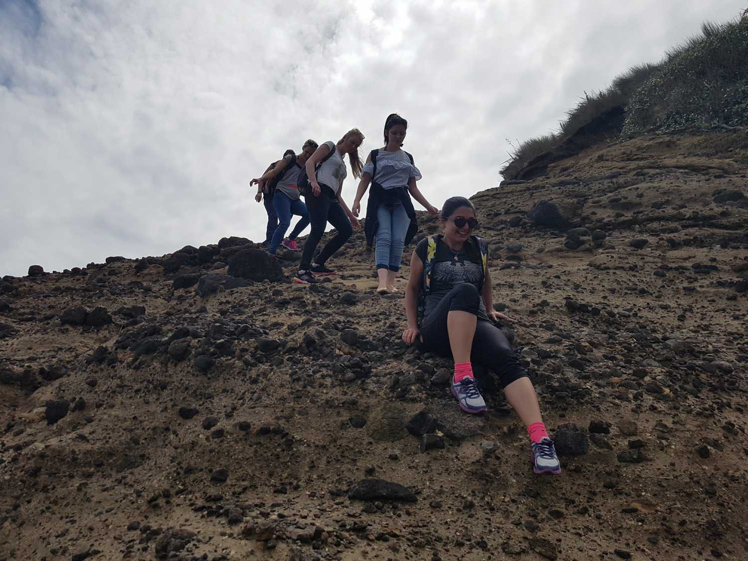 Group rock scrambling at Piha Beach
