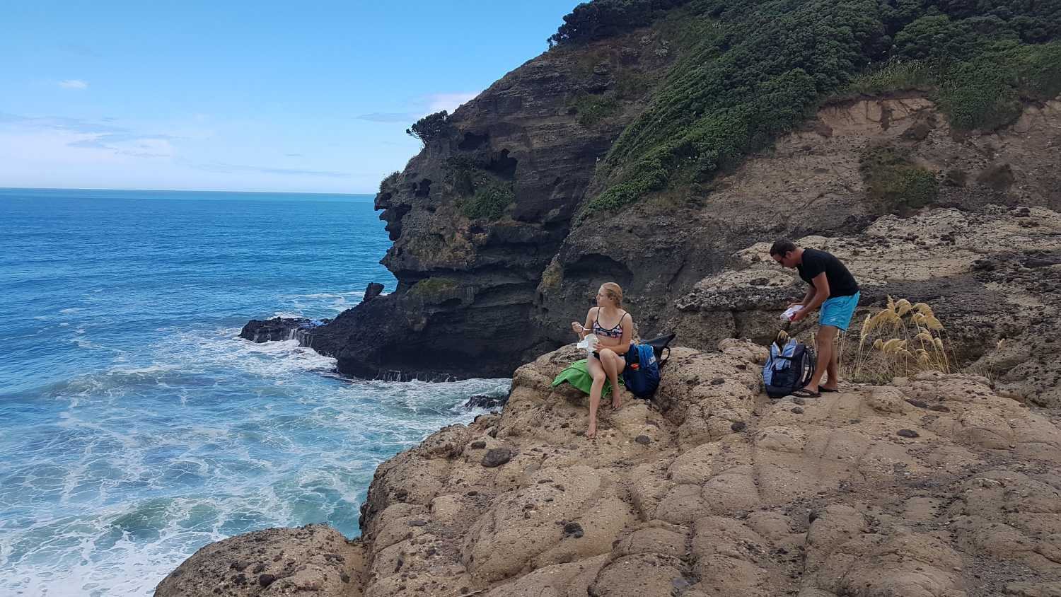 Tour group explores hidden places at Piha Beach