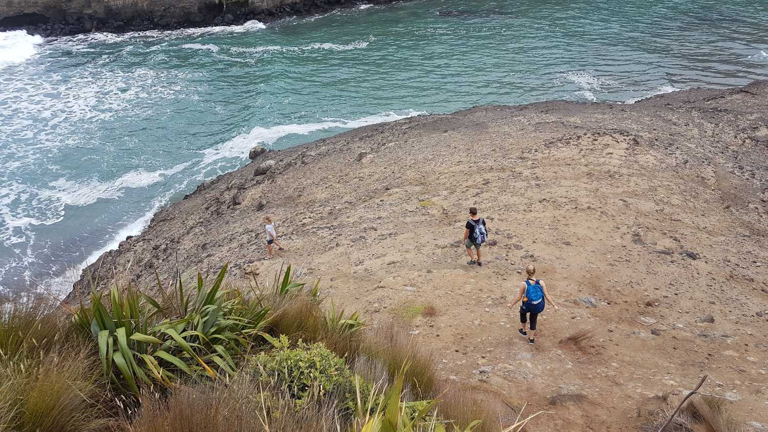 Group explores black sand beach at Piha, Auckland, NZ