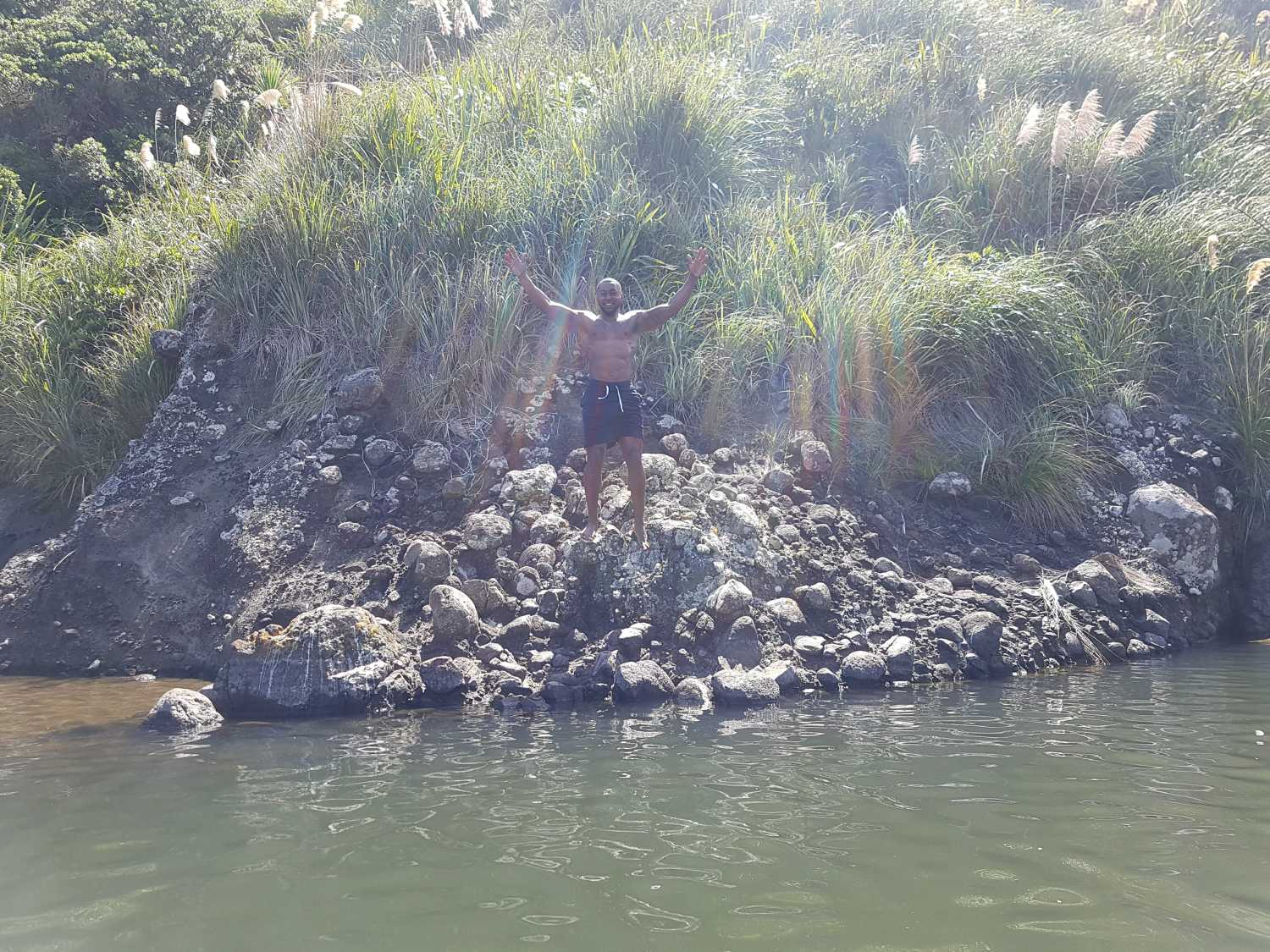 Man dives into the quiet river at Anawhata