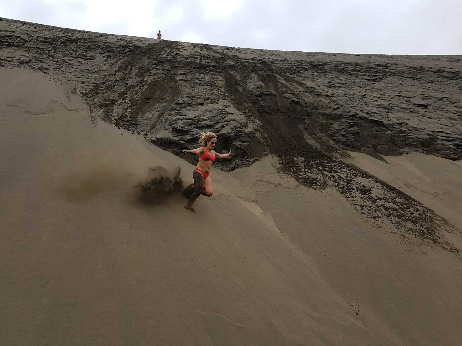 Girl sprints down the sand dunes at Bethells