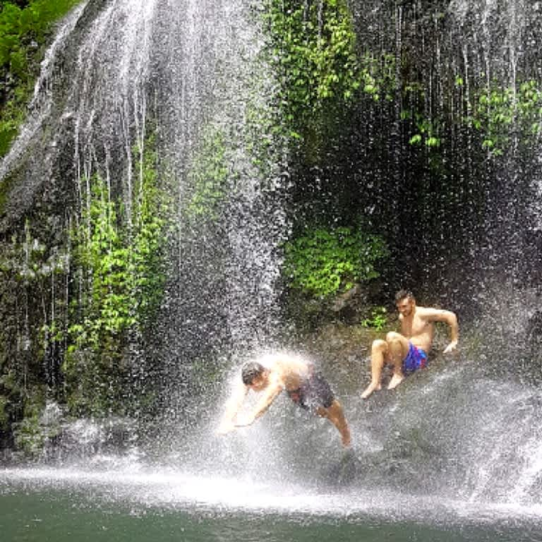 Group of backpackers diving at Kitekite Falls