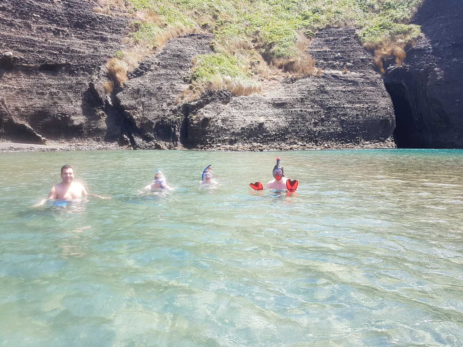 Tour group snorkelling the lagoon at Piha on a perfect day