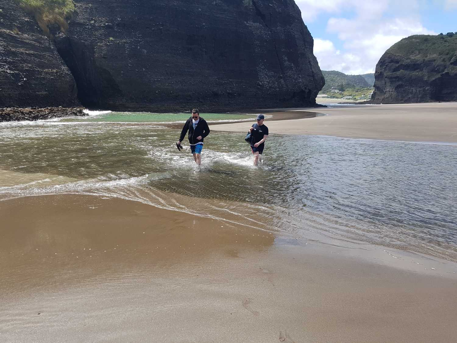Group exploring the lagoon at Piha Beach