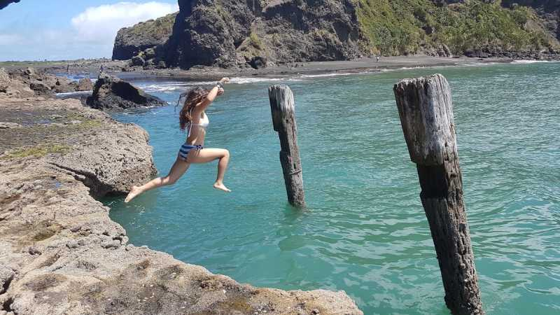 Girl leaps off the wharf for a swim at Whatipu