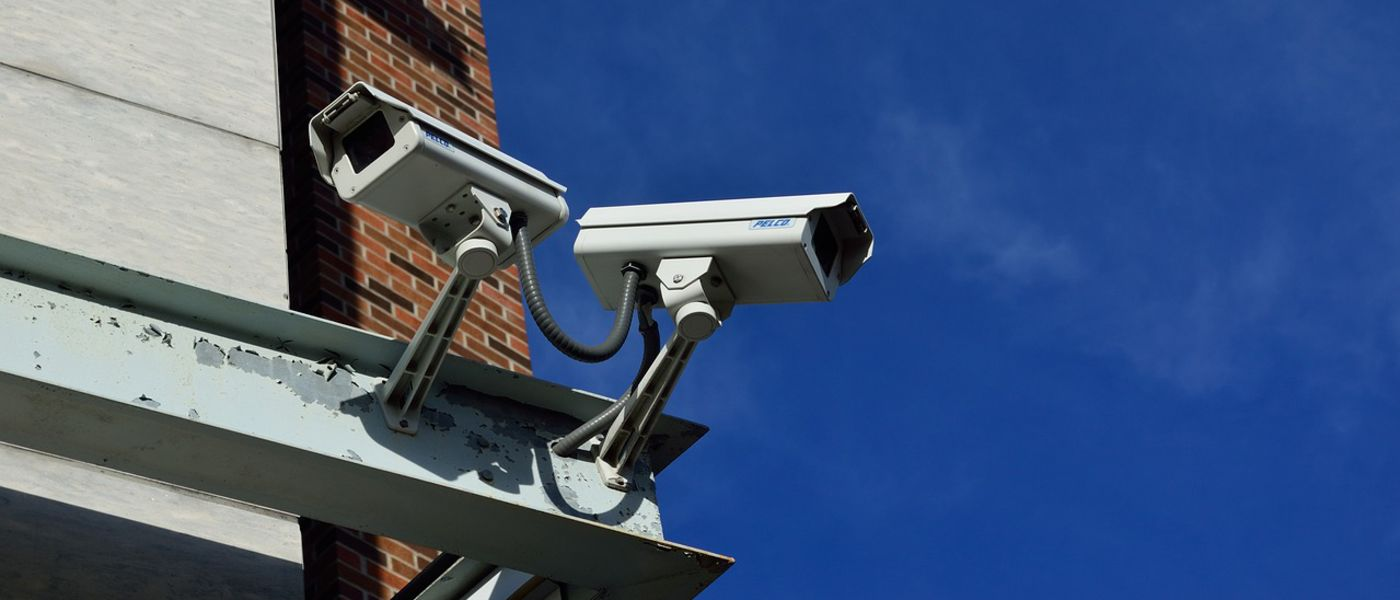 Two, building-mounted surveillance cameras facing opposite directions