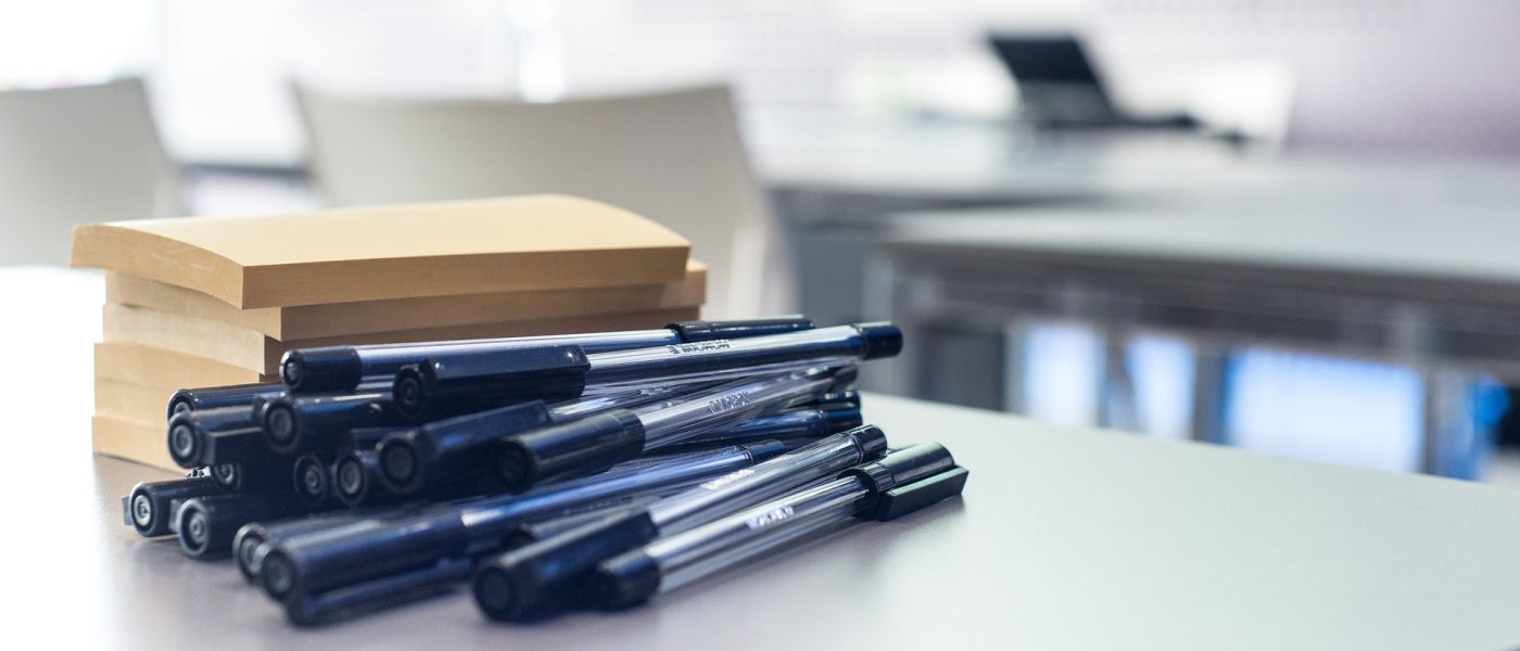 Close-up shot of pens and a stack of post-it note pads