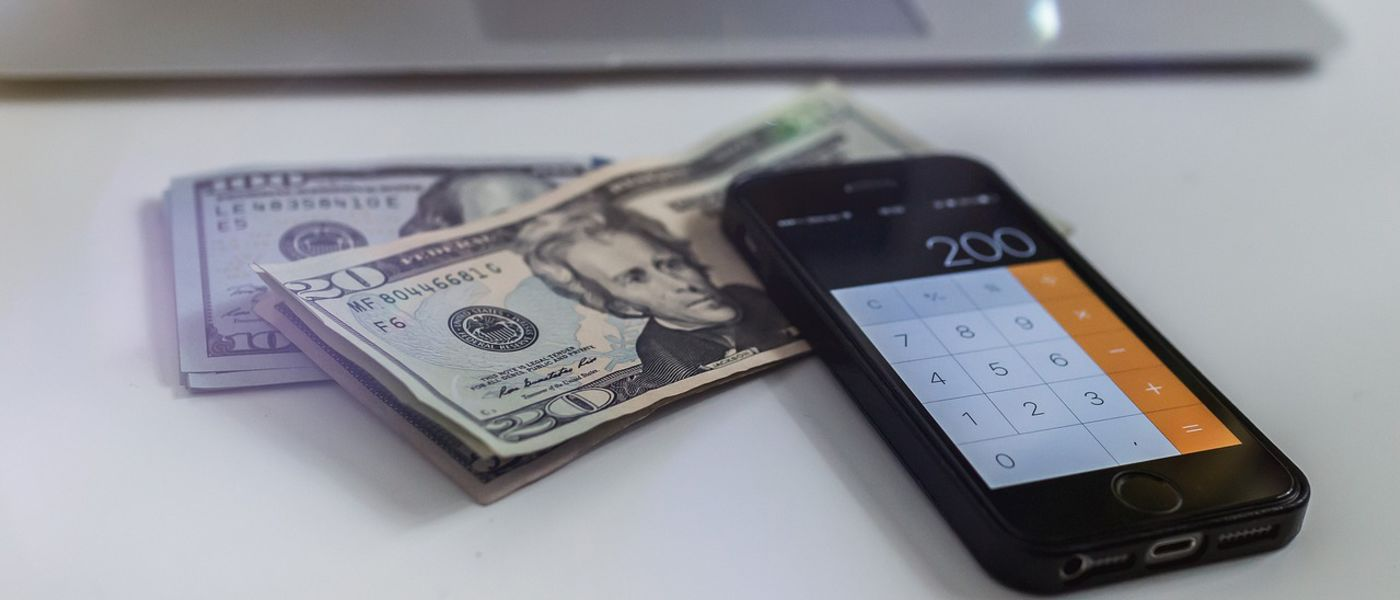 iPhone, with calculator app on-screen, sitting on top of 20 and 100 dollar bills.