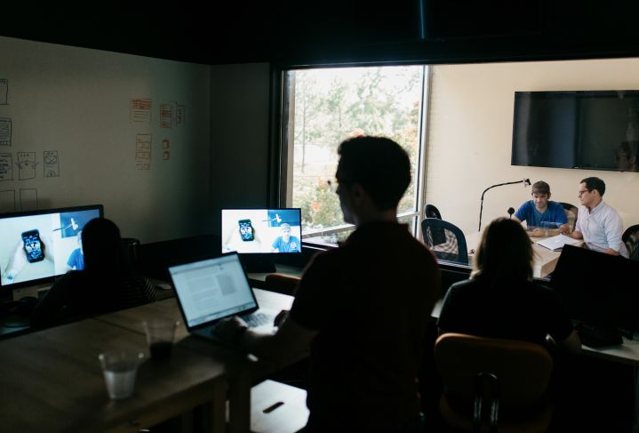 observers in the foreground in WillowTree's Usability lab, while user research is conducted in the adjoining room