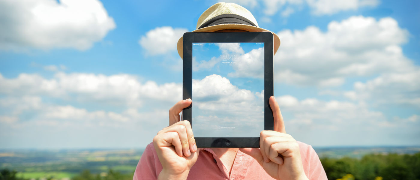 Man in a hat holding an iPad in front of his face, with pictures of clouds that match the clouds in the sky behind his head