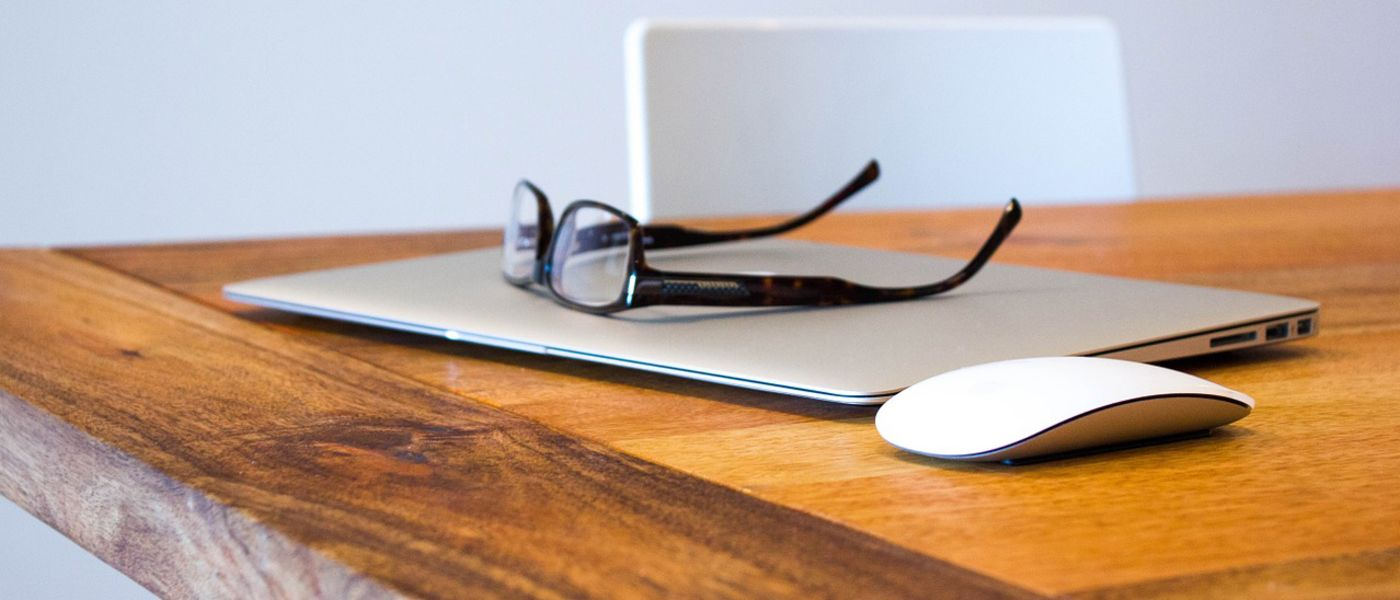 Eyeglasses sitting atop a MacBook laptop, next to an Apple Magic Mouse on a wood table.