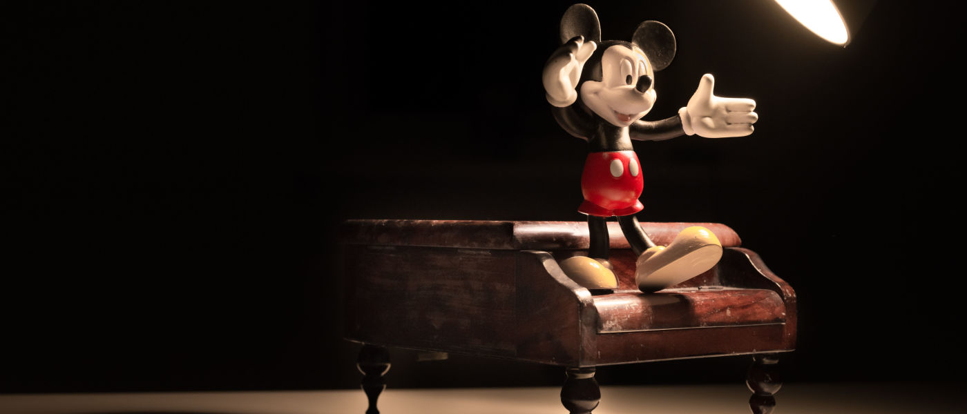 photo of cartoon mouse standing on miniature piano