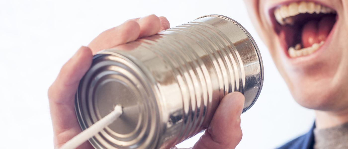 person speaking into tin can phone