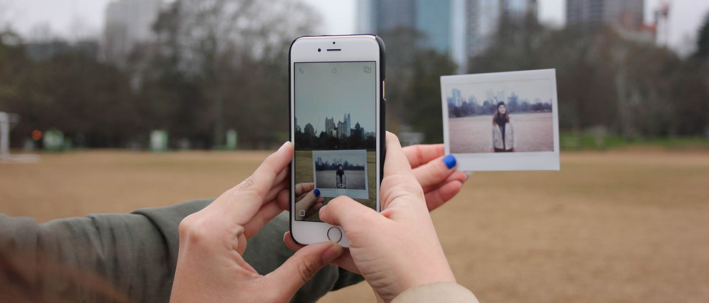 hands holding an iPhone, taking a picture of a Polaroid photograph with a city skyline in the background