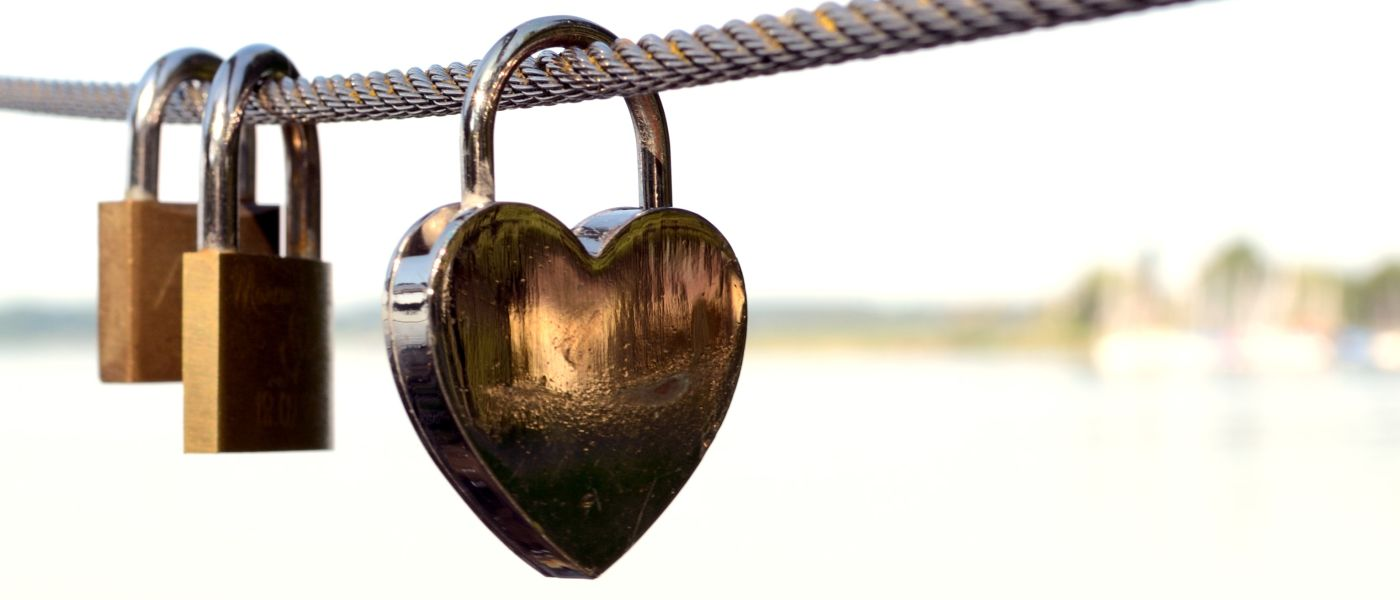 Close-up shot of heart-shaped lock and two other locks hanging from a steel cable