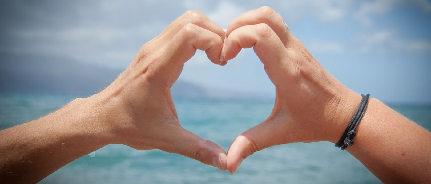 Two hands forming the shape of a heart with the ocean in the background.