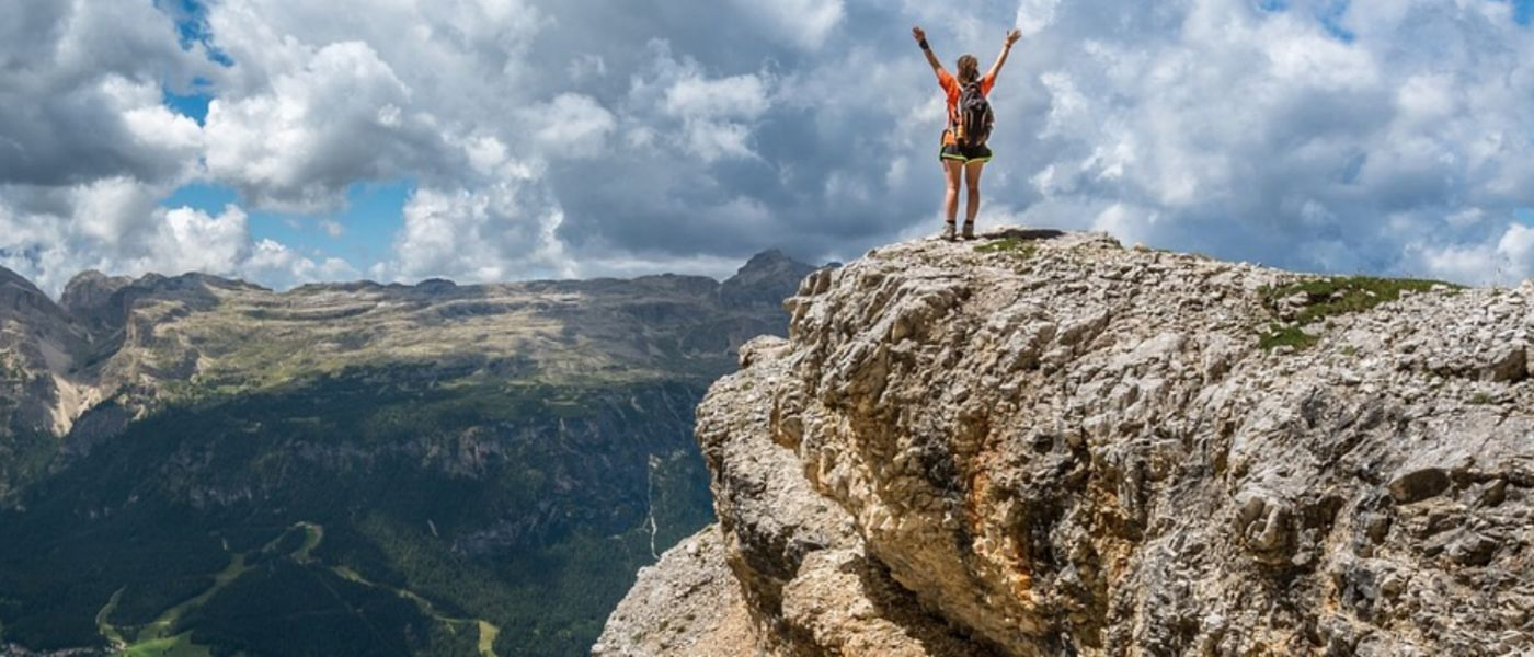beautiful vista with person standing on mountaintop with arms in the air