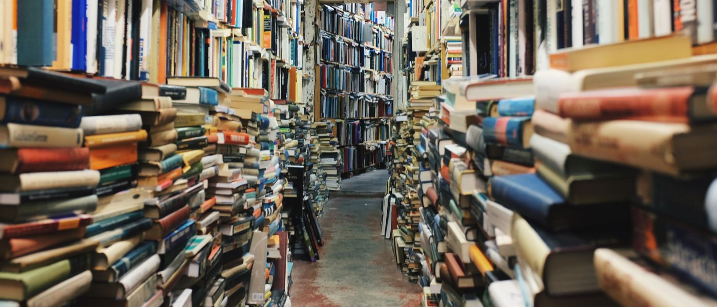 View down a long, curving aisle of cluttered bookshelves.