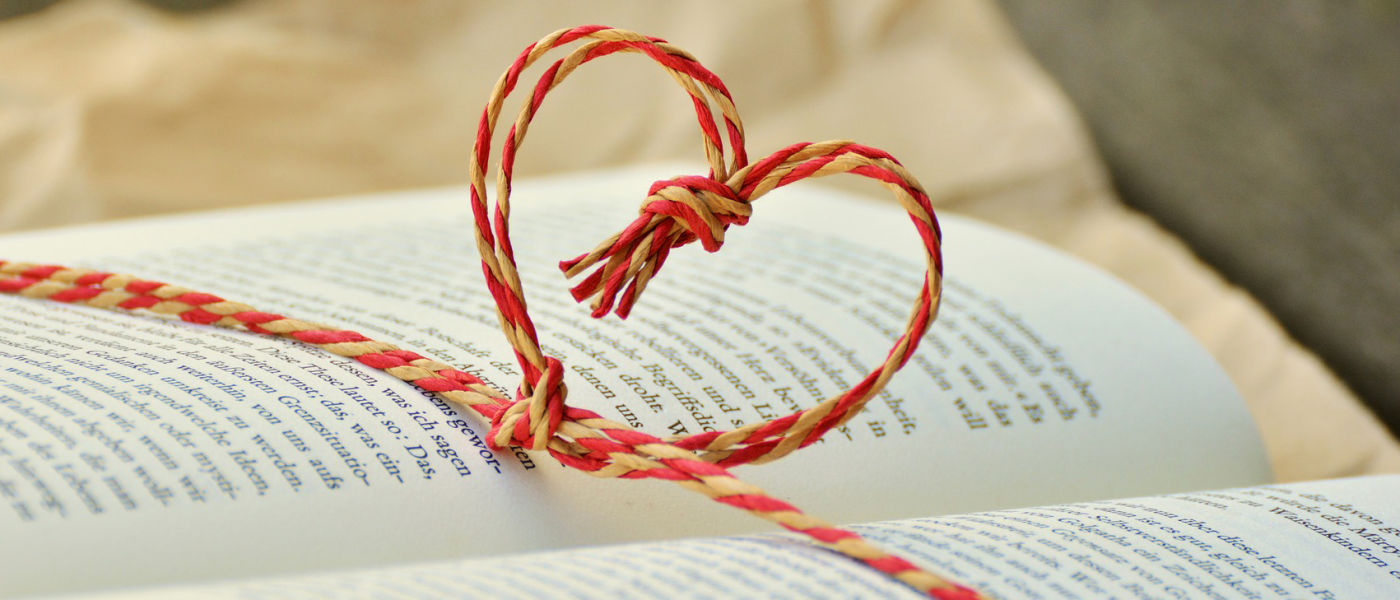 Red and white string tied in a heart-shaped knot around an open book.
