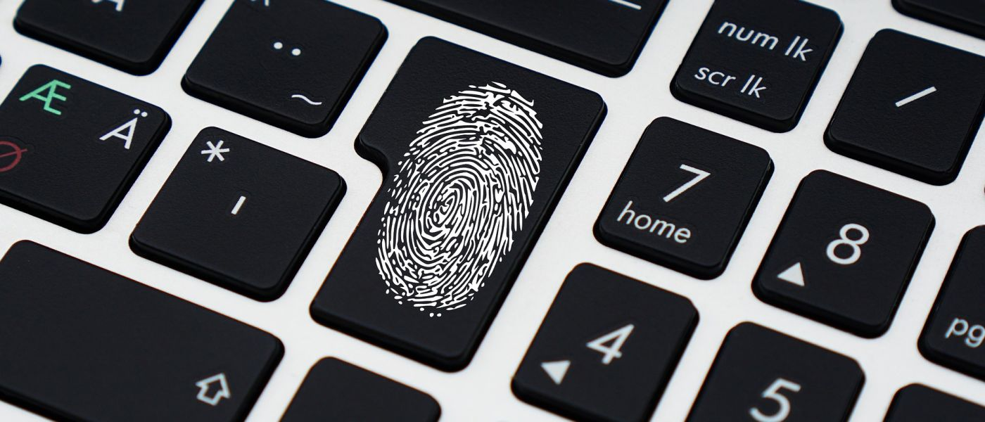 Image of a fingerprint superimposed on the return key of a laptop keyboard.