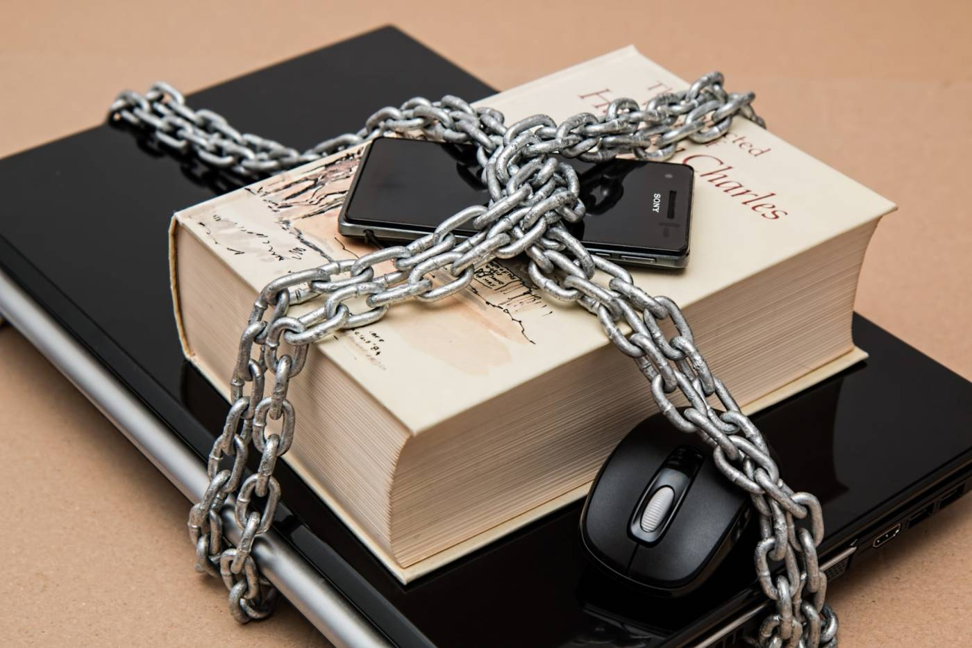 Phone, book, laptop, mouse chained together