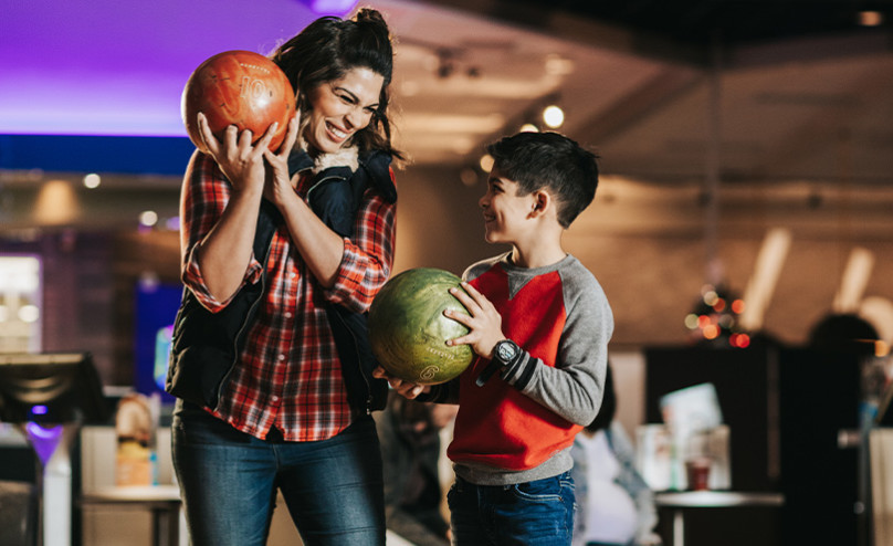 Mom bowling with son