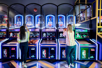 Women playing Basketball game in gaming area