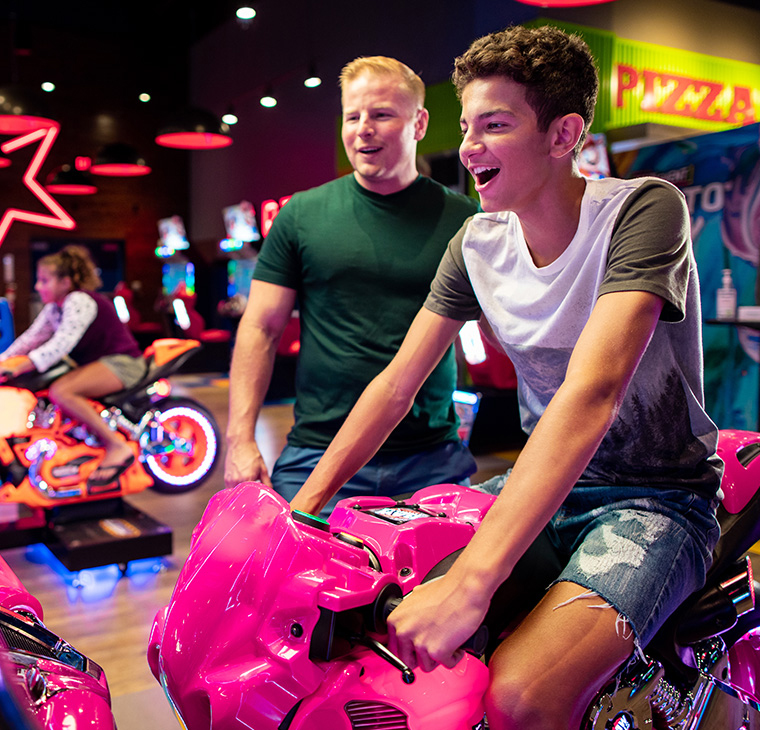 People playing motorcycle arcade game