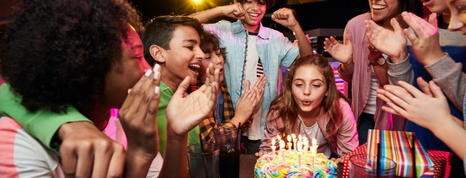 Girl blowing out candles at party
