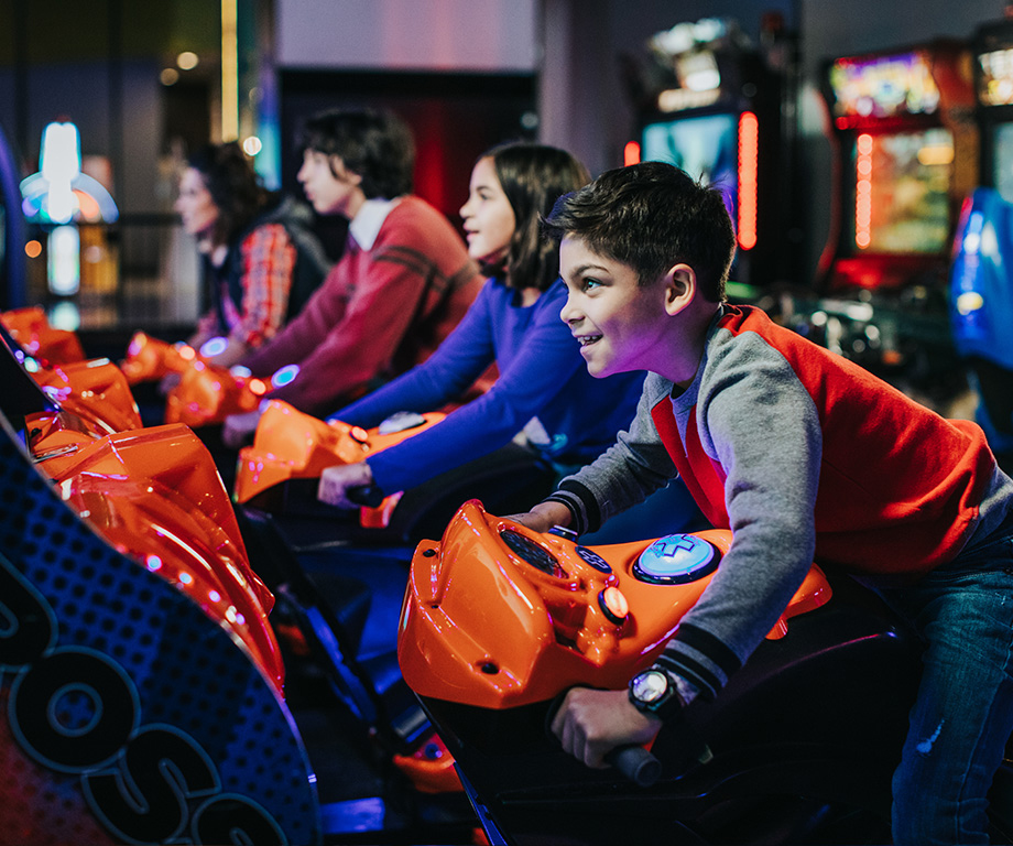 Kids playing motorcycle arcade game