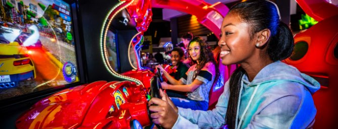 Teens playing driving arcade game