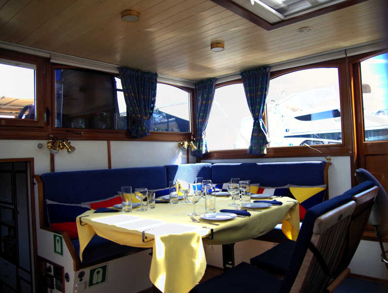 Salon with blue benches and dining table on the Löcknitz yacht