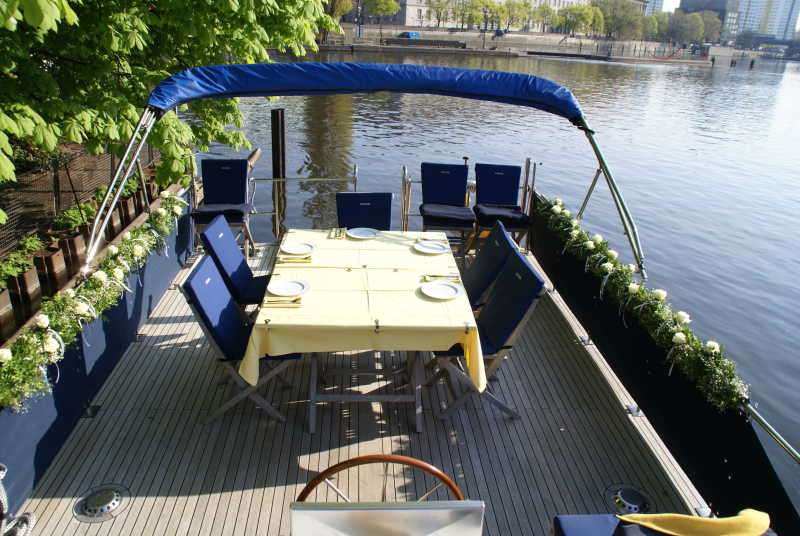 Sundeck with dining table and chairs on the motorboat Löcknitz in Berlin