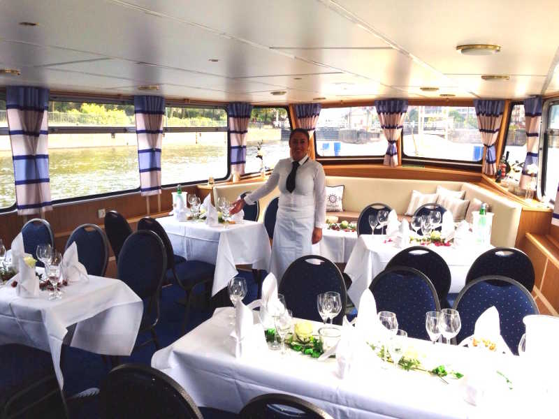 Lower deck with laid tables and service personnel on the Bon Ami ship