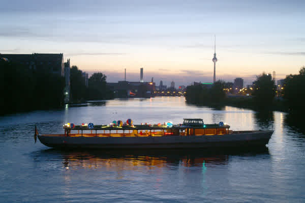 Party boat Stralau in the sunset with Berlin skyline in the background