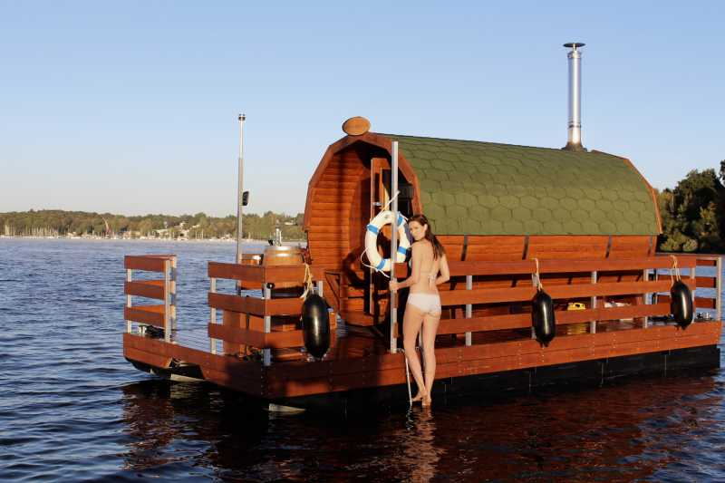 Sauna raft on the Wannsee with a young lady in a bikini on the bathing ladder