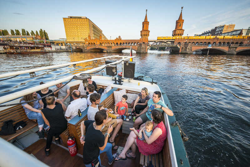 Open stern area of ​​the ship Josi with party guests in front of the Oberbaum Bridge