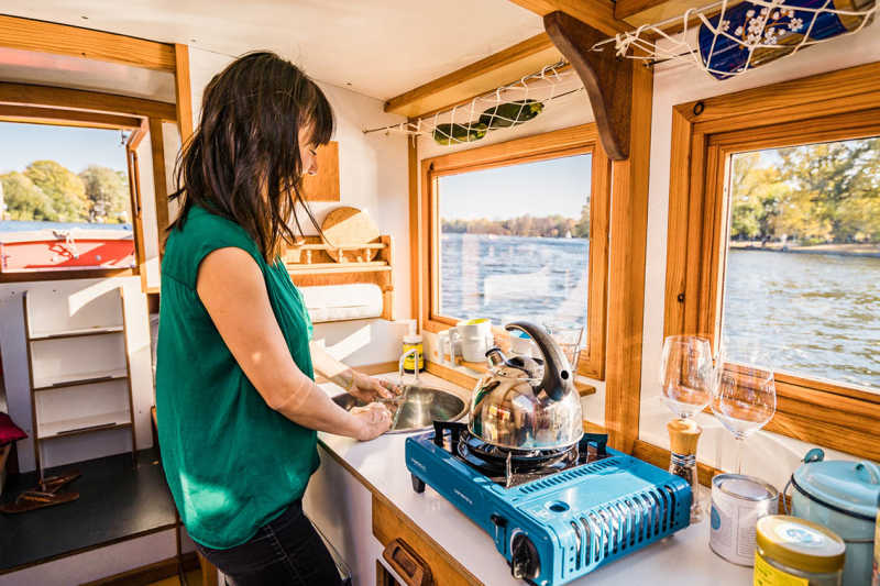 A woman cooks in the kitchen of the houseboat Wasserkutsche