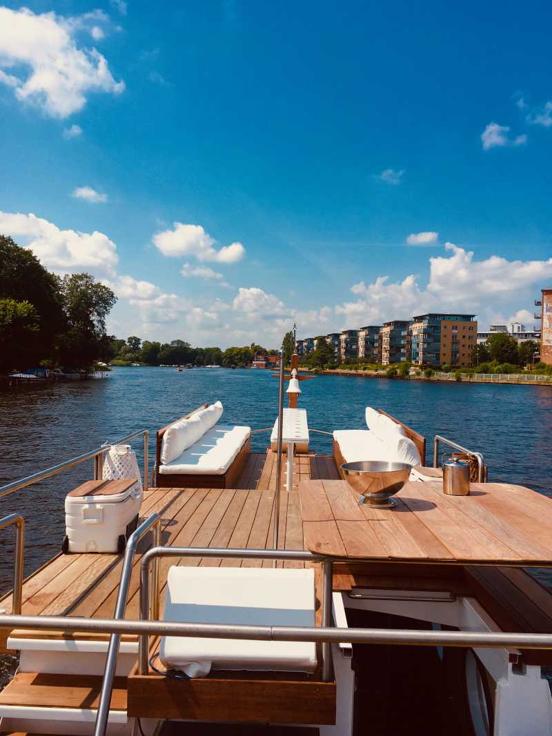 Boat tour on the upper deck of the party boat Geilezeit with lounge furniture and a view of the Spree
