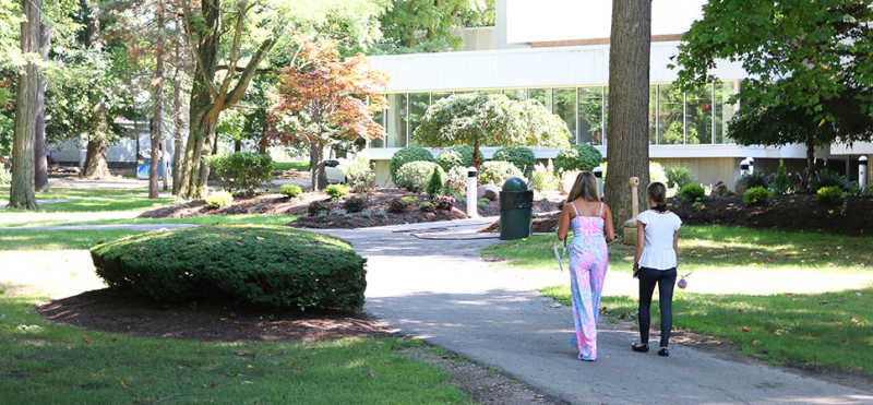 two students walking through Lake Erie College campus on a sunny day