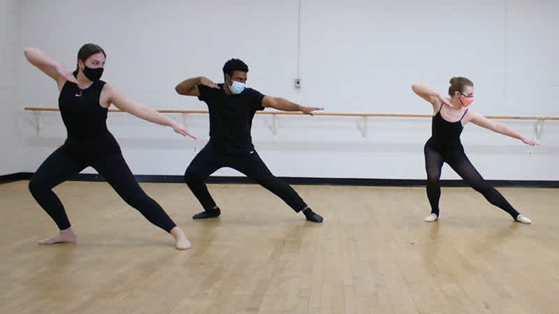 Three young dancers, wearing all black and masks.
