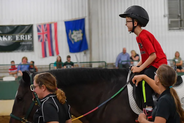 a young boy riding a black horse wearing a red t-shirt