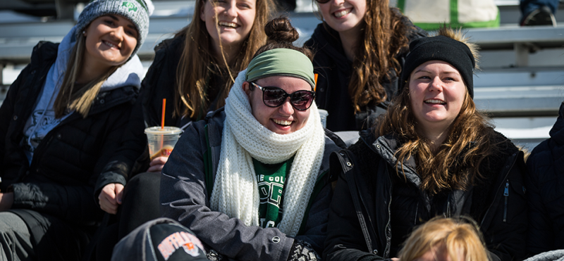 Lake Erie College students sitting in bleachers wearing winter coats