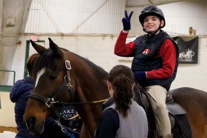 young female rider in a red shirt making a peace sign while riding a horse