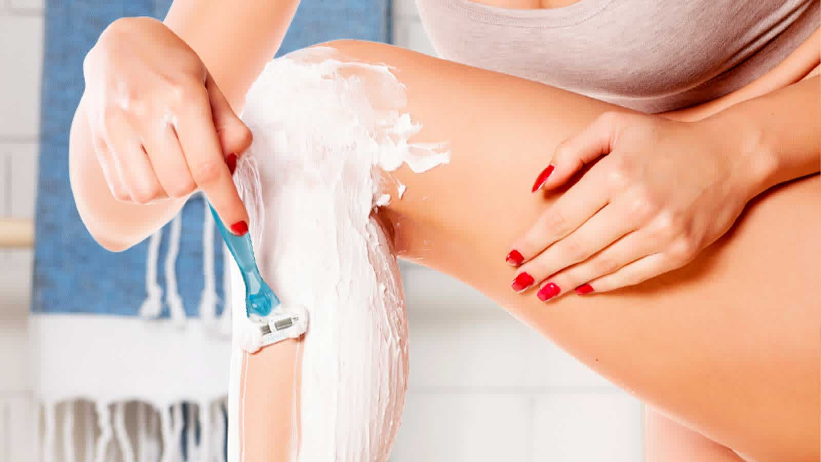 Woman Using Shaving Gel or Cream for Legs Shaving in the Bath